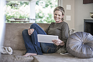 Smiling woman sitting on couch looking at digital tablet - ZEF007684
