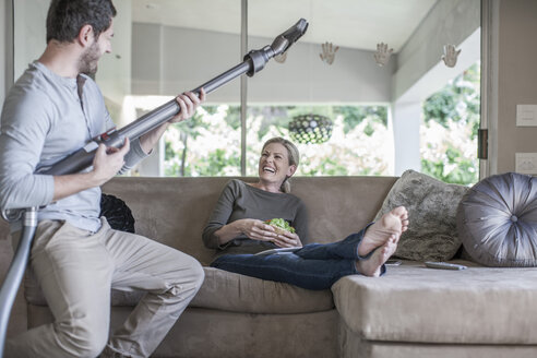 Woman on couch and man pretending playing guitar with vacuum cleaner - ZEF007690