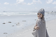 Portrait of smiling woman wearing beanie and wrap on the beach - ZEF007720