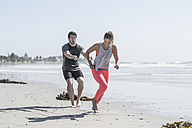 Young man and woman exercising on beach - ZEF007738