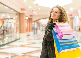 Italy, Lombardy, Milan, Woman with shopping bags in a shopping center - OIPF000040