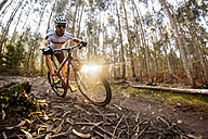 Mountain biker driving in the forest - MGOF001205