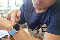 Young man using smartwatch, close-up - ABAF001970