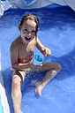 Little girl splashing with water in a paddling pool - LBF001319