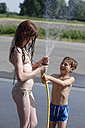 Laughing boy splashing water on his sister with garden hose in summer - LBF001325