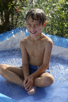 Boy sitting in a paddling pool while someone pouring water on him - LBF001328