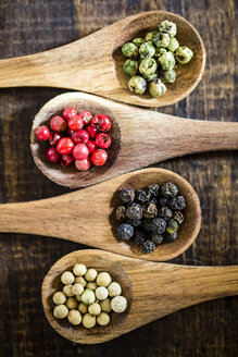 Row of four wooden spoons of different peppercorns - SARF002407