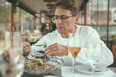 Brazil, Florianopolis, man eating fresh oysters in a restaurant - MFF002572