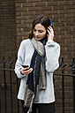 UK, London, young woman with headphones listening music from her smartphone - MAUF000176