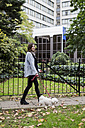 UK, London, young woman going walkies with her dog - MAUF000185