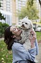 UK, London, happy young woman with her dog - MAUF000188
