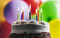 Lighted birthday candles on a cake in front of balloons - SELF000088
