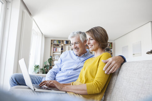 Smiling couple sitting on the couch at home using laptop - RBF003747