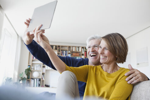 Happy couple sitting on the couch at home taking a selfie with digital tablet - RBF003759