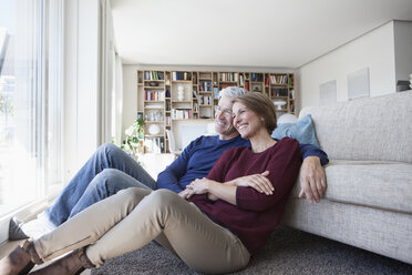 Happy couple sitting side by side on the floor of their living room - RBF003768