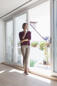 Smiling woman with cup of coffee leaning against balcony door looking at distance - RBF003771