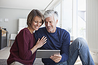 Smiling couple sitting on the floor at home looking at digital tablet - RBF003780