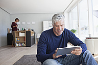 Man sitting on the floor at home using digital tablet - RBF003783