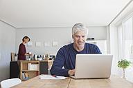 Mature man using laptop at home - RBF003789