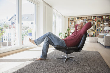 Man relaxing on leather chair at home - RBF003798