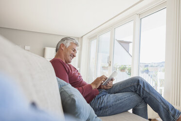 Smiling man sitting on the couch at home using digital tablet - RBF003807