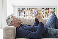 Mature man lying on the couch at home using digital tablet - RBF003813