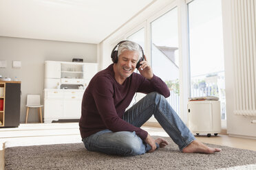 Portrait of relaxed man sitting on the floor at home hearing music with headphones - RBF003819