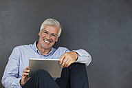 Portrait of smiling mature man with digital tablet in front of a grey wall - RBF003831
