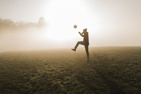 Young man playing soccer on meadow in the evening - UUF006217