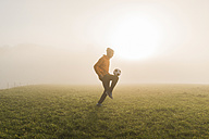 Young man playing soccer on meadow in the evening - UUF006220