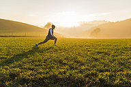 Young man stretching on meadow in the morning - UUF006241