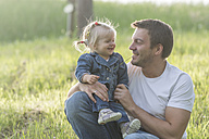 Father and his little daughter having fun on a meadow - PAF001516