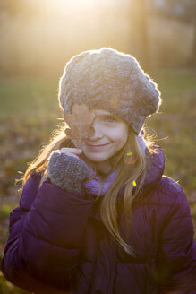 Portrait of smiling girl at evening twilight covering one eye with an autumn leaf - SARF002422
