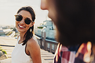 Austria, Vienna, portrait of smiling young woman with sunglasses flirting on a roof terrace - AIF000129