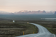 Iceland, Golden Circle, Car on country road with volcanos in background - PAF001519