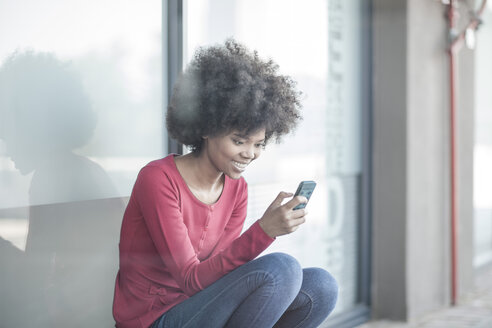 Young woman reading messages on smart phone - ZEF007805