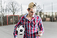 Young football player with smartphone - UUF006301