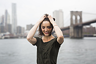USA, New York City, smiling young woman on an excursion boat on a windy day - GIOF000609