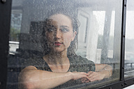 Portrait of young woman looking through window of an excursion boat on a rainy day - GIOF000612