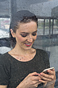 Smiling young woman behind window pane looking at her smartphone on a rainy day - GIOF000618