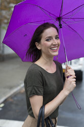 USA, New York City, portrait of smiling young woman standing with umbrella on a rainy day - GIOF000621