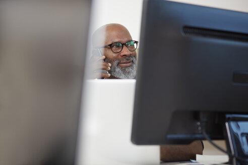 Portrait of smiling man telephoning between computer monitors - RHF001150