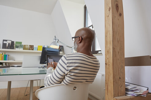 Back view of man sitting at desk of his home office using smartphone - RHF001156