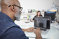 Man using laptop at his desk - RHF001162