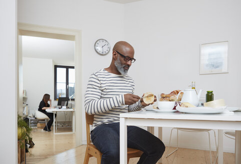 Man having late breakfast at his home office - RHF001165