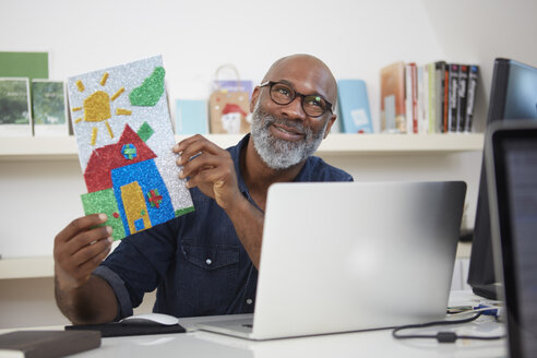 Portrait of smiling man sitting at his desk showing child's drawing - RHF001174