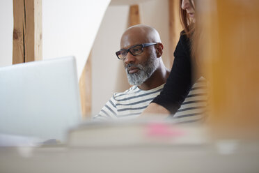 Portrait of man sitting at his desk looking at laptop - RHF001186