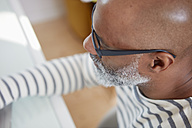 Bald man with grey beard working with laptop, close-up - RHF001189