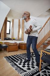 Man playing ukulele in his living room - RHF001207