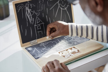Man with children's toy notebook, close-up - RHF001216
